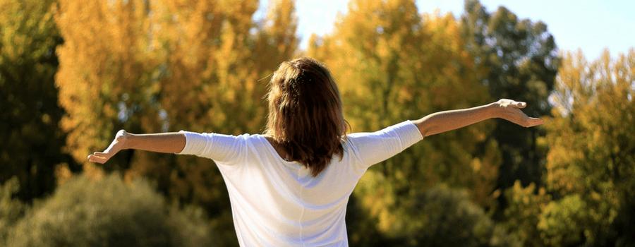 Selbstbewusstsein und Ziele, Frau vo hinten zu sehen mit hochgerissenen Armen