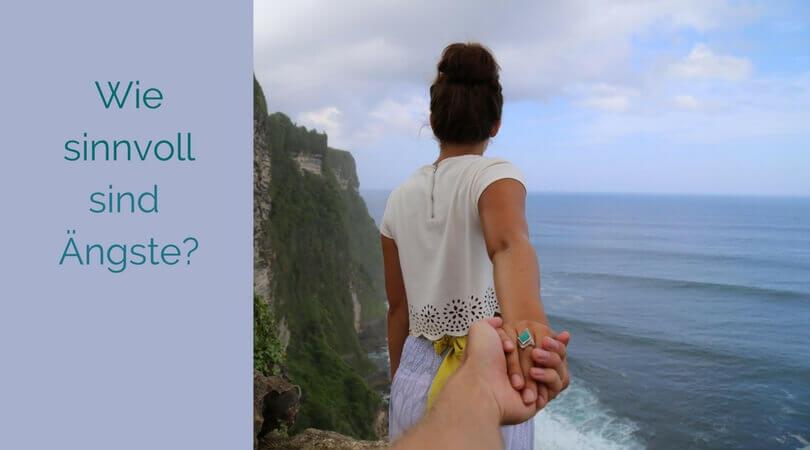 Wie sinnvoll sind Ängste, Frau steht auf einer Klippe über dem Meer, wird an der Handgehalten