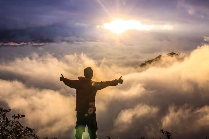 Selbstbewusstsein, junger Mann steht selbstbewusst auf dem Gipfel